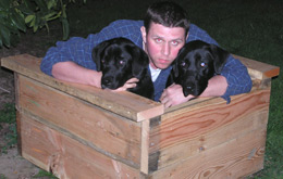 my psycho neighbor Jason mandhandling the dogs into one of my planter boxes: photo by Sienna